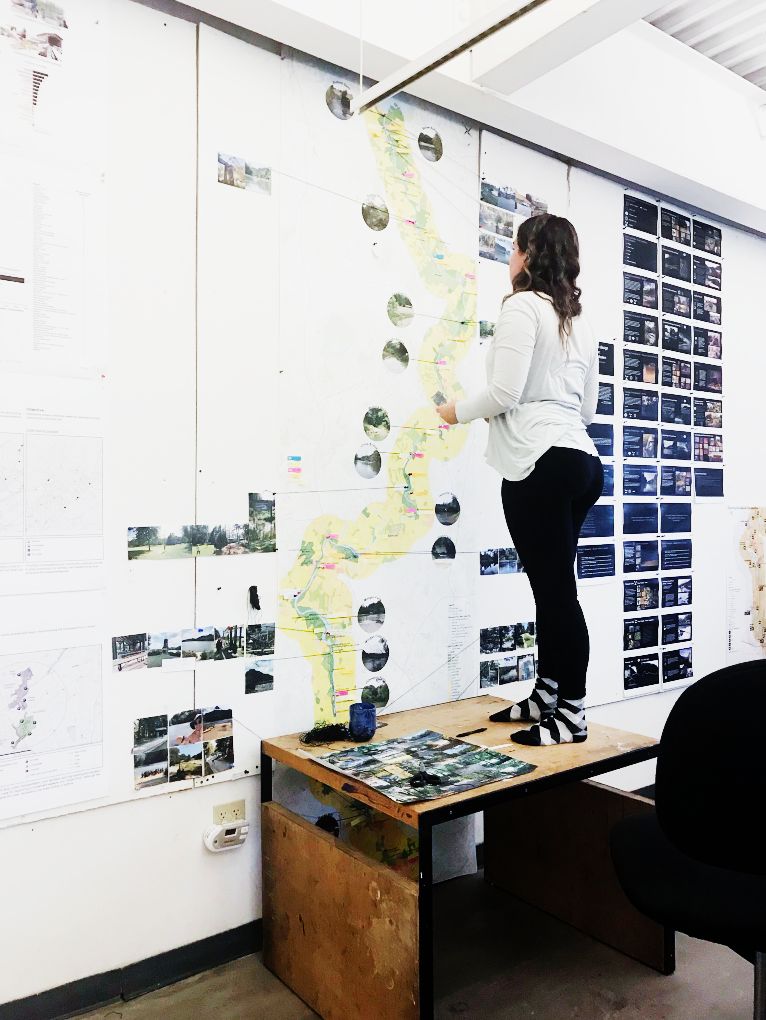 Student stands on desk to look at large scale drawing on the wall.