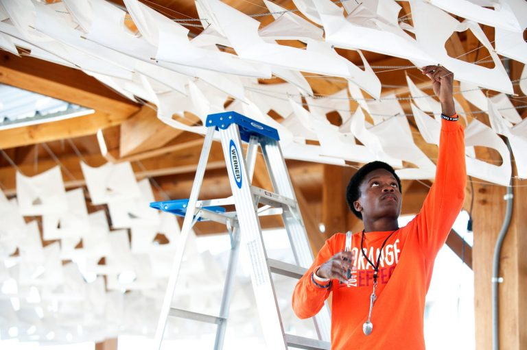 Student attaches material in outdoor installation.